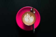 Latte chaud dans la tasse rose avec le modèle floral dans la vue supérieure de mousse sur le fond foncé Photos stock