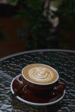 Latte chaud de café avec le bel art de latte sur le verre en céramique dans le lo Photos stock