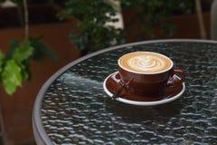 Latte chaud de café avec le bel art de latte sur le verre en céramique dans le lo Images stock