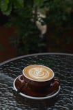 Latte chaud de café avec le bel art de latte sur le verre en céramique dans le lo Image stock