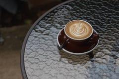 Latte chaud de café avec le bel art de latte sur le verre en céramique dans le lo Photo libre de droits