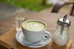 Latte chaud de Matcha dans la tasse blanche avec de l'eau boissons en verre et sucre dans la bouteille sur la table en bois Photos libres de droits