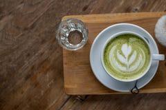 Latte chaud de thé vert de Matcha dans la tasse blanche du plat en bois avec de l'eau certain en verre sur la table en bois Images libres de droits