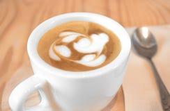 Latte chaud, sur la table en bois, le fond de tache floue, l'art de latte dans la forme de coeur, l'amour et le concept romantiqu Photo libre de droits
