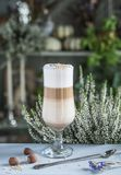 Latte chestnut in a beautiful glass and antique spoon on table on the background of heather stock image