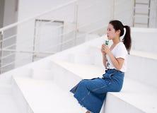 Latte cinese asiatico della bevanda dello studente universitario sul campo da giuoco Fotografie Stock Libere da Diritti