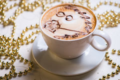 Latte coffee. With decorative Christmas beads in background stock images