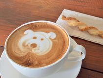Latte Coffee art and biscuit stick on the wooden desk. Royalty Free Stock Photo