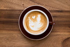 A Latte Coffee art on the wooden desk Royalty Free Stock Photos