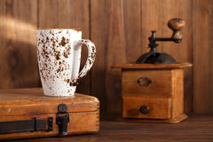 Latte coffee cup with Nostalgic coffee grinder on background. Latte coffee cup with Nostalgic coffee grinder and old wood on background Stock Photo