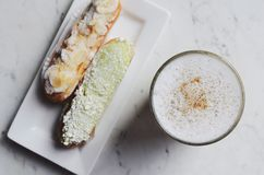 Latte coffee and eclairs at the cafe table Royalty Free Stock Images