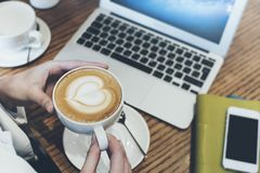Latte coffee in female hands , a businessman working on a laptop background , hipster in a cafe with a cup of coffee and a gadget stock photos