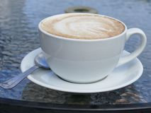 Latte coffee. A full cup of latte coffee in a white cup and saucer with Royalty Free Stock Photo
