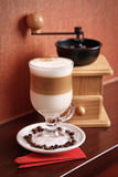 Latte and coffee-grinder. Composition with Latte and coffee-grinder royalty free stock images