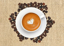 Latte coffee with heart symbol over roasted coffee beans Stock Photography
