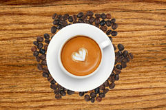 Latte coffee with heart symbol over roasted coffee beans Stock Images