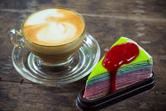 Latte coffee and rainbow crape cake with strawberry sauce Royalty Free Stock Photography