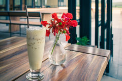 Latte Coffee And summer flowers are in the glass. Stock Photo