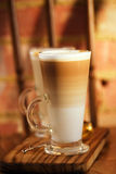 Latte coffee in tall glasses on vintage chair with old brick wal Stock Photo