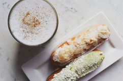 Latte topped with cinnamon and cardamom and two eclairs Royalty Free Stock Images