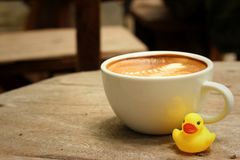 Latte coffee with yellow rubber duck on background of wooden. Royalty Free Stock Image