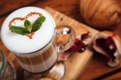 Latte com os doces na tabela de madeira Fotografia de Stock Royalty Free