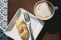 Latte con arte y rollo cubano del queso para el desayuno con Sun caliente imagenes de archivo