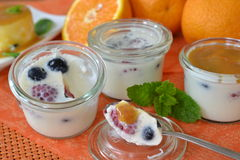Latte cotta with berries and orange sauce. Small glasses of latte cotta with berries and orange sauce, one partially eaten Stock Photos
