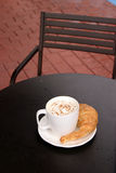 Latte with croisant outside on red brick. Latte with croisant and whipped cream and chocolate power on an outside table on red brick in an upscale coffee shop in royalty free stock photos