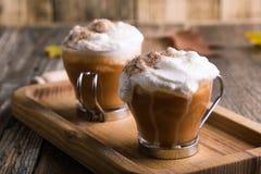 Latte d'épice de potiron avec les épices fouettées de crème et de tarte photos stock