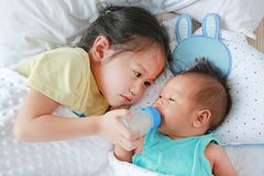 Latte d'alimentazione della sorella asiatica sveglia dalla bottiglia per il neonato che si trova sul letto immagini stock libere da diritti
