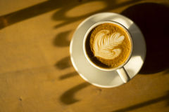 Latte da xícara de café na luminosidade reduzida Imagem de Stock