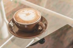 Latte da xícara de café na tabela na cafetaria, efeito do filtro do vintage Foto de Stock Royalty Free