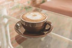 Latte da xícara de café na tabela na cafetaria, efeito do filtro do vintage Fotos de Stock