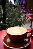 Latte dans la tasse brune sur la table rouge image libre de droits