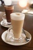 Latte de café en glace grande contre un hublot Image stock