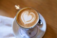 Latte de Caffe avec le modèle de mousse de forme de coeur Image stock