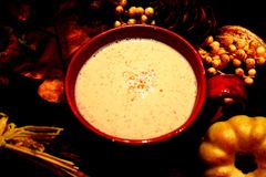 Latte de chute dans la tasse et des feuilles rouges photo stock