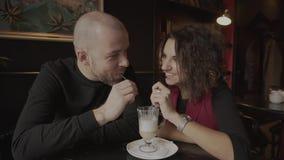 Latte de consumición de los pares felices jovenes a partir de una taza en un café metrajes