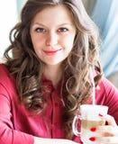 Latte de consumición hermoso del café de la mujer joven en un café Imagenes de archivo