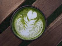 Latte de Matcha en una taza en la tabla de madera fotos de archivo
