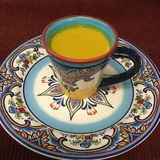 Latte de oro de la cúrcuma en taza y placa de cerámica españolas de café Fotografía de archivo