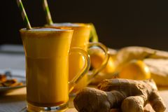 Latte de safran des indes ou lait d'or en verres avec du gingembre et des citrons sur une table blanche photo stock
