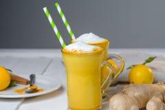 Latte de safran des indes ou lait d'or en verres avec du gingembre et des citrons sur une table blanche image stock