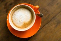 Latte del café en taza anaranjada con textura de madera Imagenes de archivo