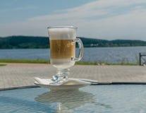 Latte del caffè in un calice di vetro alto Sullo sfondo naturale Immagini Stock Libere da Diritti