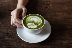 Latte del tè verde della tenuta della mano fotografie stock