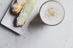 Latte and eclairs with copy space on marble background Royalty Free Stock Photo