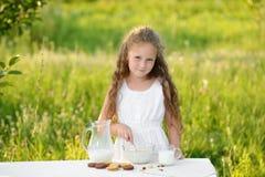 Latte della bambina sveglia e cereale di versamento di fabbricazione per fare colazione estate all'aperto Fotografie Stock Libere da Diritti