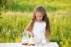 Latte della bambina sveglia e cereale di versamento di fabbricazione per fare colazione estate all'aperto Fotografie Stock